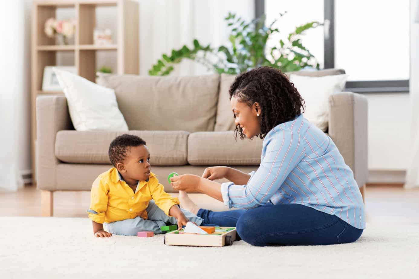 mom and toddler sitting on floor playing getting ready to get toddler excited about cleaning up the toys