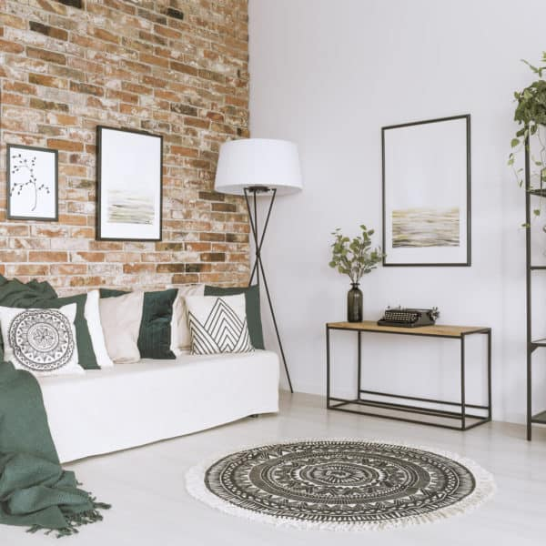 Cushions and blankets on white sofa in cozy living room with pictures on brick wall