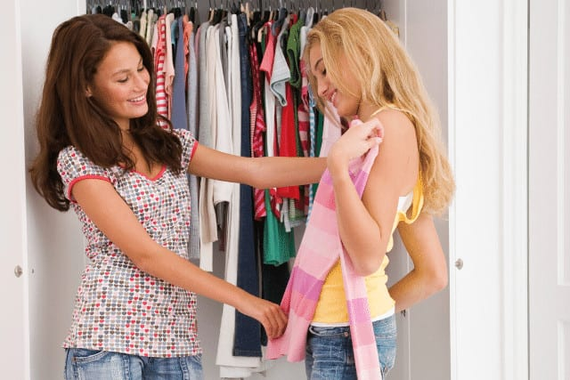 girls decluttering clothes in closet