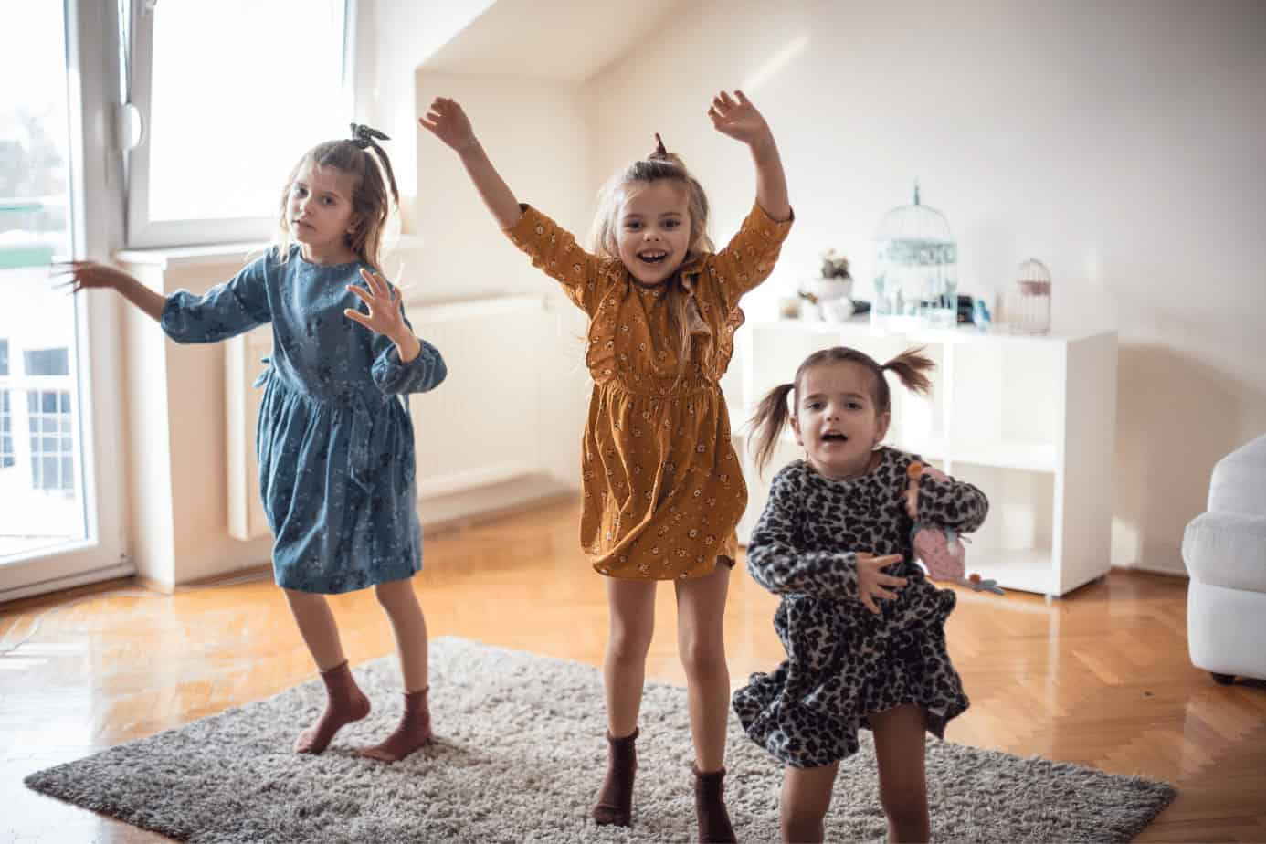 three little girls dancing excited about cleaning up toys
