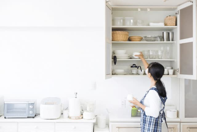 lady decluttering kitchen cabinet one