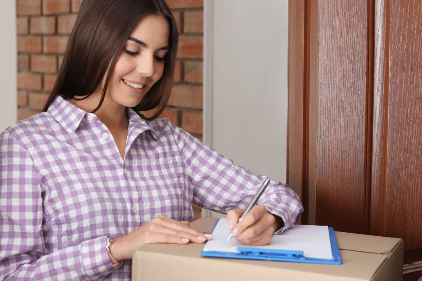 lady using checklist on clipboard sitting on box decluttering