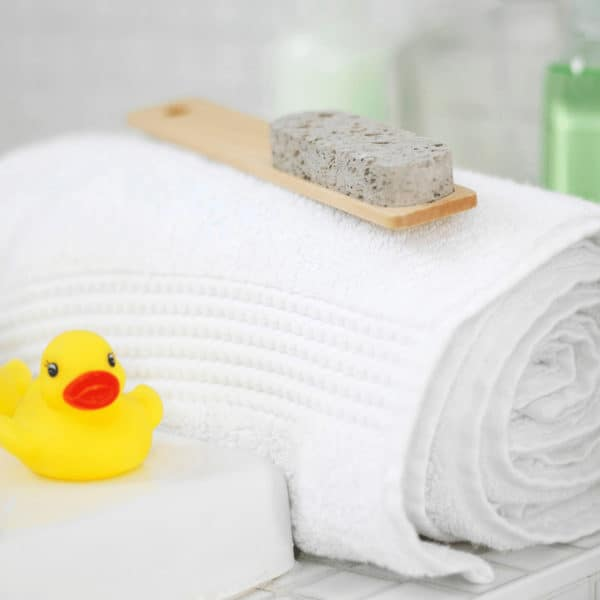 rolled bath towels rubber ducks sitting on side of bathtub for deep clean bathroom post