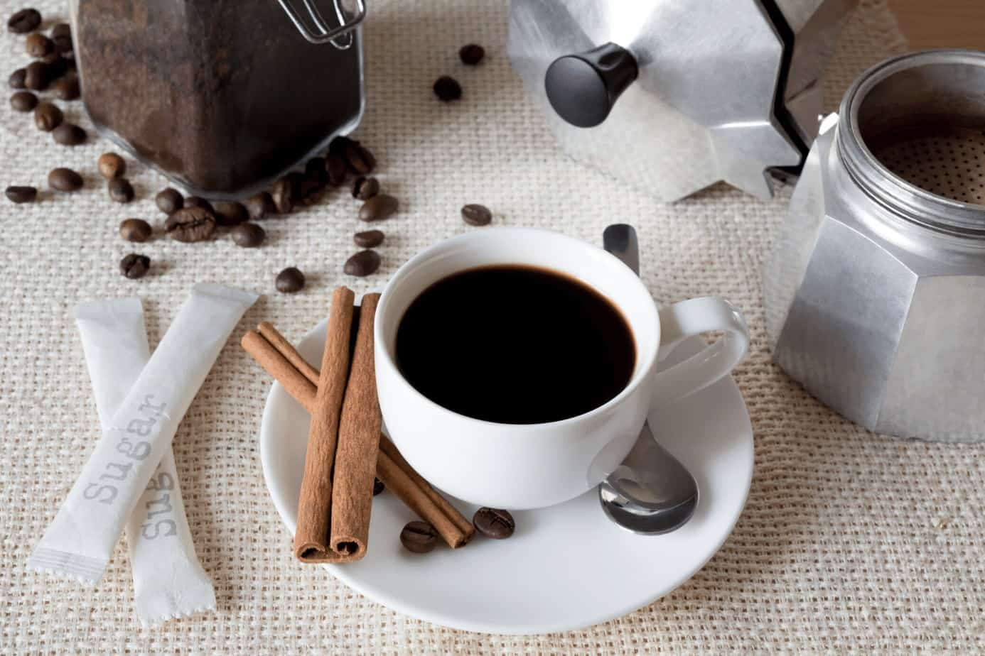 cup of coffee and coffee beans with cinnamon sticks