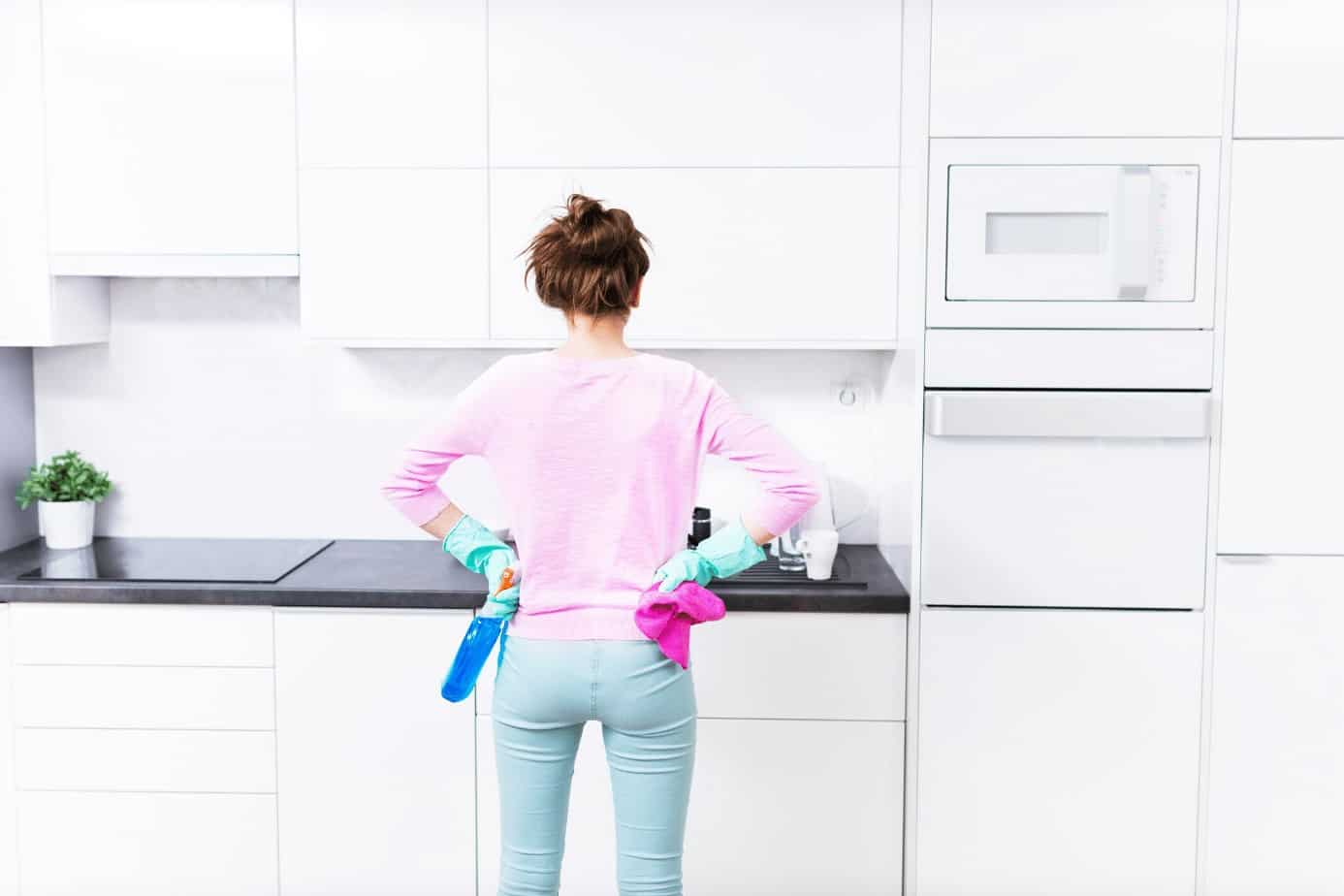 lady facing kitchen cabinets with cleaning gloves on