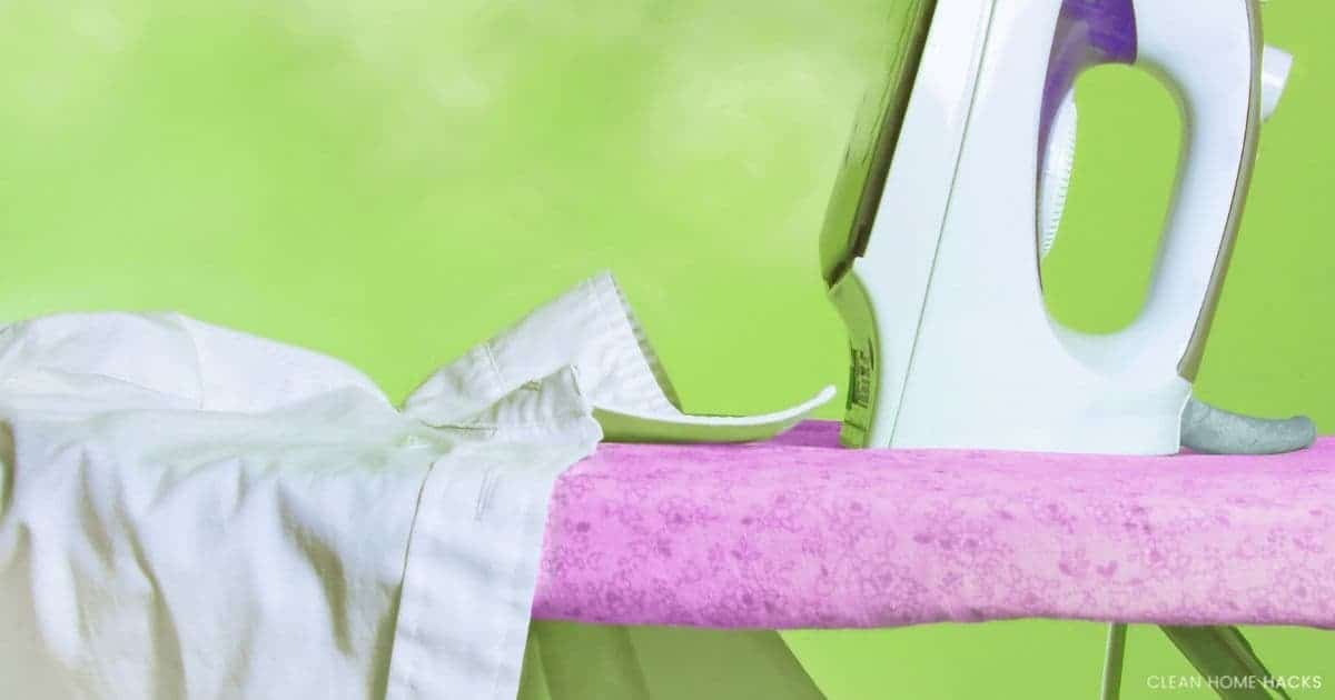 pink cover on wall mounted ironing board green background and white iron